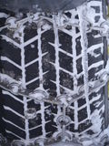 Le plan rapproché du pneu de voiture attachent avec la chaîne Photographie stock libre de droits