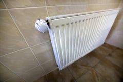 Le plan rapproch? du radiateur de chauffage blanc avec l'ion de valve de thermostat a couvert de tuiles les murs et le fond de pl photo stock