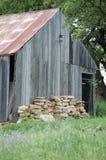 Le plance mancanti del vecchio granaio si sono sbiadite entro tempo ed il tempo ha arrugginito tetto della latta Immagine Stock