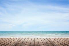 Le plancher en bois avec la mer et le ciel a brouillé le fond Images stock