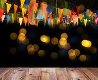 Le plancher en bois et les drapeaux colorés au-dessus du bokeh pour la nuit font la fête le décor Image stock