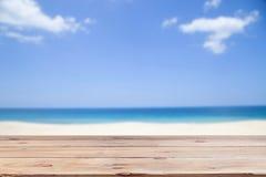 Le plancher en bois sur le ciel d'espace libre de tache floue et l'île échouent le fond d'été Photographie stock