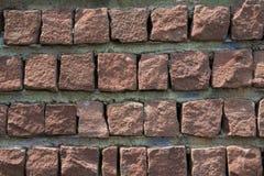 Le plancher rougeâtre urbain a ajusté les blocs en pierre avec la texture concrète photo stock