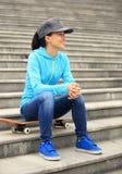 Le planchiste de femme s'asseyent sur des escaliers Images libres de droits