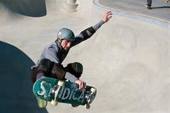 Le planchiste de vétéran attrape l'air dans la cuvette au nouveau parc de planche à roulettes Photo libre de droits