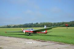 Le planeur argenté et rouge se tient sur la piste d'atterrissage d'herbe dans le petit aéroport de pays tandis que le temps est a Photos libres de droits