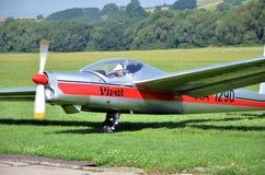Le planeur argenté et rouge se tient sur la piste d'atterrissage d'herbe dans le petit aéroport de pays tandis que le temps est a Image libre de droits