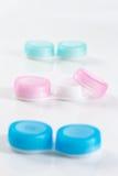 Le plastique bleu et rose entre en contact avec la caisse sur le fond blanc image libre de droits
