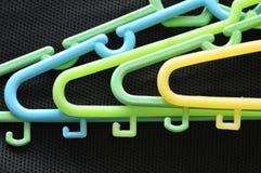 Le plastique coloré vêtx la faim recouverte sur le tissu noir photographie stock