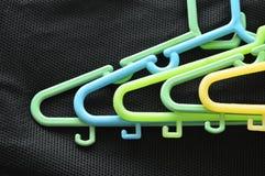 Le plastique coloré vêtx la faim sur le tissu noir image stock