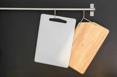 Le plastique et le bois de planche à découper accrochent sur la barre Photos libres de droits
