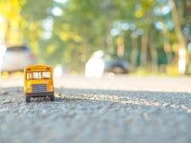 Le plastique et le métal jaunes d'autobus scolaire jouent le modèle sur le pays roa Photo stock