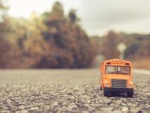 Le plastique et le métal jaunes d'autobus scolaire jouent le modèle sur le pays roa Images stock