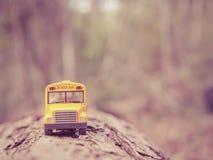 Le plastique et le métal jaunes d'autobus scolaire jouent le modèle sur le pays roa Photos libres de droits