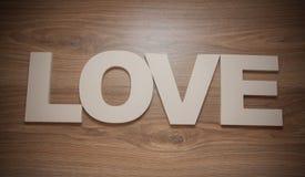Le plastique marque avec des lettres l'amour sur le fond en bois Images stock