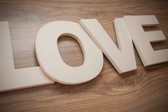 Le plastique marque avec des lettres l'amour sur le fond en bois Image stock