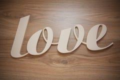 Le plastique marque avec des lettres l'amour sur le fond en bois Photos libres de droits