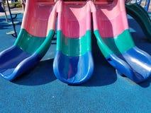 Le plastique multicolore glisse sur le terrain de jeu photographie stock libre de droits