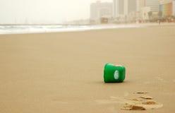 Le plastique peut sur la plage vide Photo libre de droits