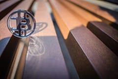 Le plastique voient la pièce de monnaie mordue sur le fond en bois images stock
