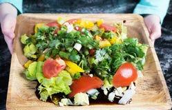 Le plat avec de la salade de légumes frais La fille montre le plat Photos stock