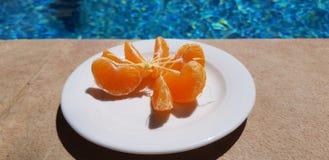 Le plat avec les tranches épluchées de mandarine se tiennent près de la piscine extérieure bleue photographie stock libre de droits