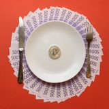 Le plat blanc avec des couverts et un bitcoin de pièce sur la nappe est fait d'euro billets sur le fond rouge photo stock