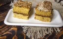 Le plat blanc avec le biscuit coupé en tranches durcit sur les conseils en bois foncés Photos stock