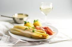 Le plat blanc juteux d'asperge avec des pommes de terre et le jambon sur un blanc plat Images stock