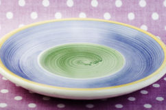 Le plat bleu et vert vide sur le rose a pointillé le fond Image stock