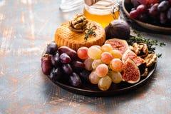 Le plat de fromage a servi avec des raisins, la confiture, les figues, le miel et les écrous sur un fond rustique Copiez l'espace photographie stock