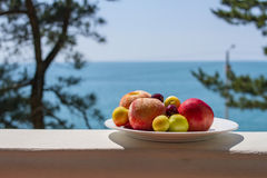 Le plat de fruit avec les pêches mûres, les cerises juteuses et les prunes sur la plage se reposent sur un balcon en bois sur le  Image stock