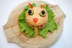 Le plat en bois d'ion de monstres d'hamburger de Halloween, nourriture pour des enfants font la fête photo stock