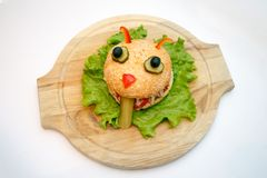 Le plat en bois d'ion de monstres d'hamburger de Halloween, nourriture pour des enfants font la fête photographie stock
