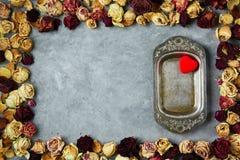 Le plat en métal de vintage dans le cadre des roses sèches bourgeonne sur le fond concret gris Photographie stock libre de droits