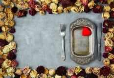 Le plat en métal de vintage dans le cadre des roses sèches bourgeonne sur le fond concret gris Image stock