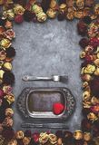 Le plat en métal de vintage dans le cadre des roses sèches bourgeonne sur le fond concret gris Photo libre de droits