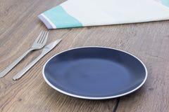 Le plat, la serviette de tissu et les couverts bleus vides ont placé sur la table en bois images stock