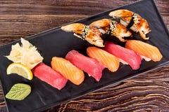 Le plat noir des sushi de nigiri, se ferment  Image stock