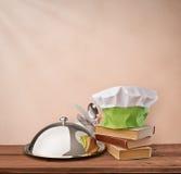 Le plateau de nourriture, le chef de chapeau et le cuisinier réservent sur un fond beige de vintage Photographie stock