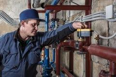 Le plombier ajuste l'équipement dans le sous-sol Photos stock