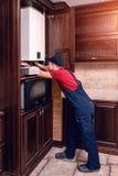 Le plombier ajuste la chaudi?re de gaz avant d'op?rer, professionnel de son m?tier images stock