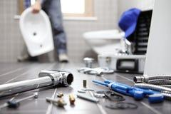 Le plombier au travail dans une salle de bains, mettant d'aplomb le service des réparations, se réunissent images libres de droits