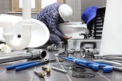 Le plombier au travail dans une salle de bains, mettant d'aplomb le service des réparations, se réunissent image stock