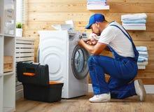 Le plombier d'ouvrier répare la machine à laver dans la blanchisserie image stock