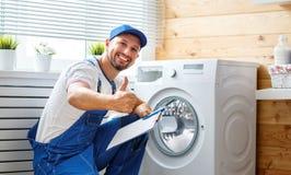 Le plombier d'ouvrier répare la machine à laver dans la blanchisserie photo stock
