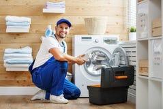 Le plombier d'ouvrier répare la machine à laver dans la blanchisserie images libres de droits