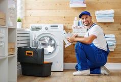 Le plombier d'ouvrier répare la machine à laver dans la blanchisserie photo libre de droits