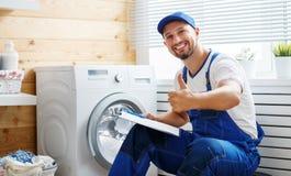 Le plombier d'ouvrier répare la machine à laver dans la blanchisserie photos stock