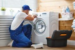 Le plombier d'ouvrier répare la machine à laver dans la blanchisserie photos libres de droits